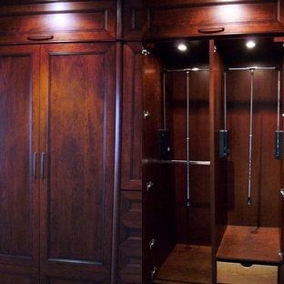 Ispirazione per una cabina armadio unisex chic di medie dimensioni con ante con riquadro incassato, ante in legno scuro e moquette