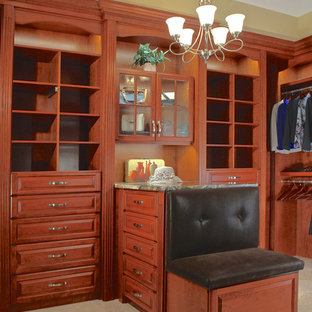 Large classic walk-in wardrobe in Chicago with raised-panel cabinets, medium wood cabinets and travertine flooring.