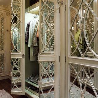 Ejemplo de vestidor de mujer, tradicional, de tamaño medio, con armarios con rebordes decorativos, puertas de armario blancas y suelo de madera en tonos medios