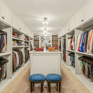 Large traditional gender-neutral walk-in wardrobe in Cleveland with recessed-panel cabinets, white cabinets, carpet and beige floor.