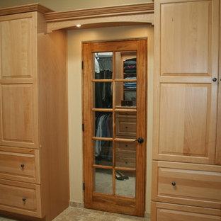 Modelo de armario vestidor unisex, de estilo americano, de tamaño medio, con armarios con paneles con relieve, puertas de armario de madera clara, suelo beige y suelo de baldosas de cerámica