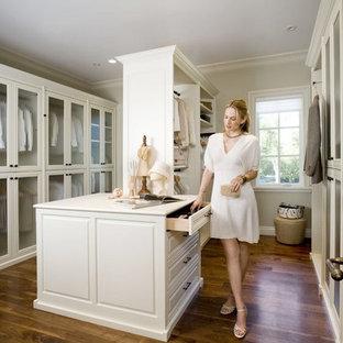 Ejemplo de armario vestidor unisex, tradicional, grande, con armarios tipo vitrina, puertas de armario blancas y suelo de madera en tonos medios