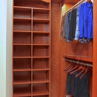Imagen de armario vestidor tradicional, grande, con armarios con paneles con relieve, puertas de armario de madera oscura y suelo de travertino