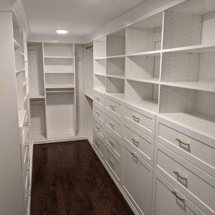 Exempel på en mellanstor klassisk garderob för könsneutrala, med luckor med infälld panel, vita skåp, mörkt trägolv och brunt golv