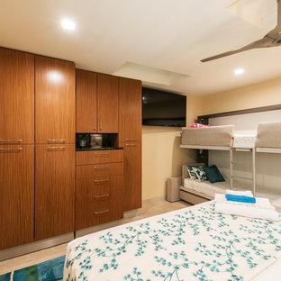 Kolonialstil Ankleidezimmer mit flächenbündigen Schrankfronten, hellbraunen Holzschränken, Kalkstein und beigem Boden in Hawaii