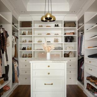 他の地域の広い女性用トランジショナルスタイルのおしゃれなウォークインクローゼット (シェーカースタイル扉のキャビネット、白いキャビネット、無垢フローリング、茶色い床、折り上げ天井) の写真