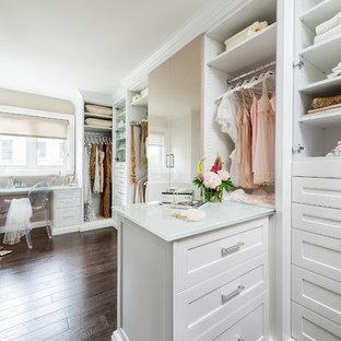 Réalisation d'un grand dressing tradition pour une femme avec un sol en bois foncé, un placard avec porte à panneau encastré, des portes de placard blanches et un sol marron.