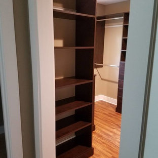 Ejemplo de armario vestidor unisex, tradicional renovado, de tamaño medio, con armarios con paneles lisos, puertas de armario de madera en tonos medios, suelo de madera clara y suelo beige