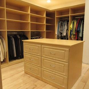 Ejemplo de armario vestidor unisex, clásico renovado, grande, con armarios con paneles con relieve, puertas de armario de madera clara, suelo de madera clara y suelo marrón