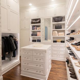 ダラスの広い女性用トランジショナルスタイルのおしゃれなウォークインクローゼット (落し込みパネル扉のキャビネット、白いキャビネット、無垢フローリング、茶色い床) の写真