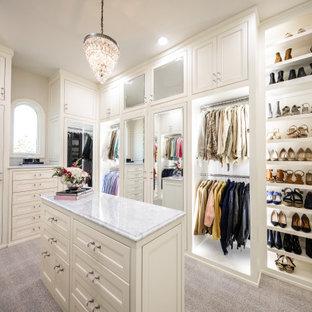 Klassisk inredning av en garderob för kvinnor, med luckor med profilerade fronter, vita skåp och vitt golv