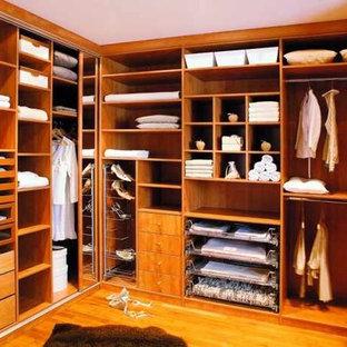 Imagen de armario vestidor unisex, tradicional renovado, de tamaño medio, con armarios abiertos, puertas de armario de madera oscura y suelo de madera en tonos medios