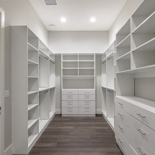 Inspiration for a large transitional gender-neutral dark wood floor and brown floor walk-in closet remodel in Orlando with flat-panel cabinets and white cabinets
