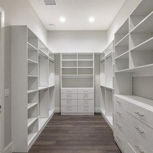 Стильный дизайн: большая гардеробная комната унисекс в стиле современная классика с плоскими фасадами, белыми фасадами, темным паркетным полом и коричневым полом - последний тренд