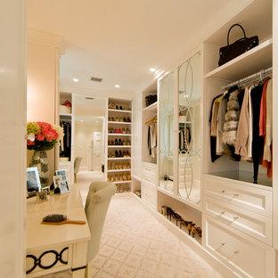 Idée de décoration pour un grand dressing room tradition pour une femme avec un placard avec porte à panneau encastré, des portes de placard blanches et moquette.