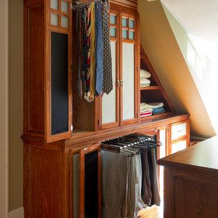Modelo de vestidor unisex, ecléctico, de tamaño medio, con armarios con rebordes decorativos, suelo de madera clara y puertas de armario de madera oscura