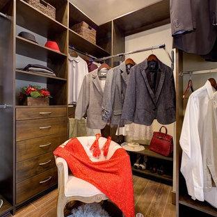 Modelo de armario vestidor de hombre, clásico renovado, de tamaño medio, con puertas de armario de madera en tonos medios, suelo de baldosas de porcelana y armarios con paneles lisos