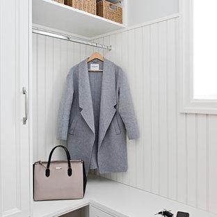 Modelo de armario vestidor unisex, tradicional renovado, pequeño, con armarios con rebordes decorativos, puertas de armario blancas, suelo de madera oscura y suelo marrón