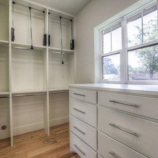 Ejemplo de armario vestidor unisex, retro, de tamaño medio, con armarios con paneles lisos, puertas de armario blancas, suelo de madera en tonos medios y suelo marrón