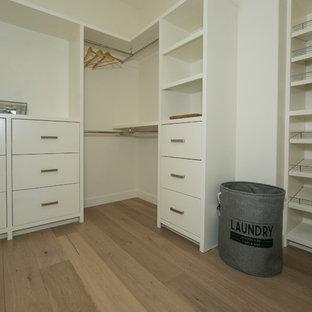 Idee per una grande cabina armadio unisex design con ante lisce, ante bianche e parquet chiaro