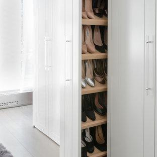 Diseño de armario y vestidor de mujer, actual, con armarios con paneles empotrados, puertas de armario blancas, suelo de madera clara y suelo gris