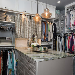 Medium sized classic gender neutral walk-in wardrobe in Austin with recessed-panel cabinets, white cabinets, travertine flooring and grey floors.