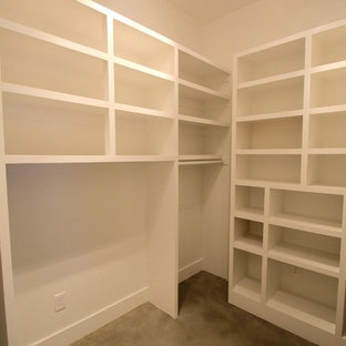 Small minimalist gender-neutral concrete floor and gray floor walk-in closet photo in Other with open cabinets and white cabinets