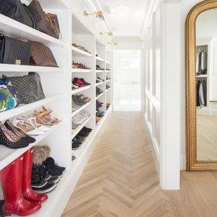 Klassisk inredning av ett walk-in-closet för könsneutrala, med öppna hyllor, vita skåp, ljust trägolv och brunt golv