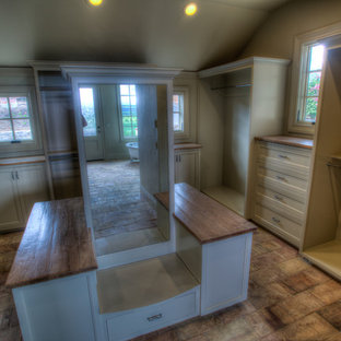 Walk-in closet - huge eclectic gender-neutral terra-cotta floor walk-in closet idea in Portland with flat-panel cabinets and white cabinets