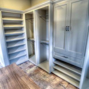 Diseño de armario vestidor unisex, ecléctico, extra grande, con armarios con paneles lisos, puertas de armario blancas y suelo de baldosas de terracota