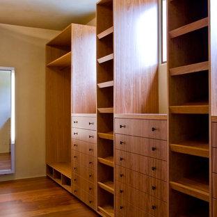 Foto de vestidor tropical, extra grande, con armarios con paneles con relieve, puertas de armario de madera en tonos medios, suelo de madera oscura y suelo marrón