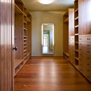 Inspiration pour un très grand dressing room ethnique avec un placard avec porte à panneau surélevé, des portes de placard en bois sombre, un sol en bois foncé et un sol marron.