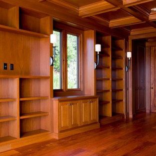 Modelo de vestidor exótico, extra grande, con armarios con paneles con relieve, puertas de armario de madera en tonos medios, suelo de madera oscura y suelo marrón