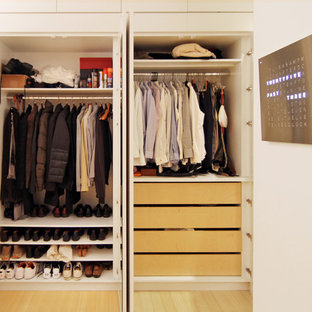 This is an example of a mid-sized modern men's built-in wardrobe in New York with open cabinets, white cabinets, bamboo floors and beige floor.