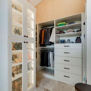 Design ideas for a large mediterranean gender neutral dressing room in Denver with flat-panel cabinets, beige cabinets, travertine flooring and beige floors.