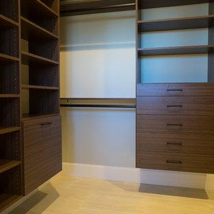 マイアミの広い男女兼用地中海スタイルのおしゃれな壁面クローゼット (フラットパネル扉のキャビネット、濃色木目調キャビネット、ライムストーンの床、ベージュの床) の写真
