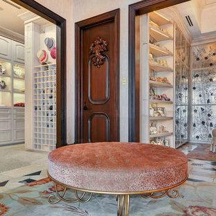 Ispirazione per un'ampia cabina armadio unisex mediterranea con ante di vetro, ante con finitura invecchiata, moquette e pavimento beige