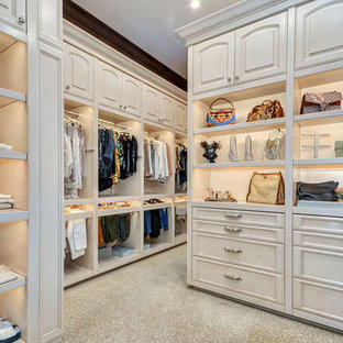 Photo of an expansive mediterranean gender-neutral walk-in wardrobe in Tampa with raised-panel cabinets, distressed cabinets, carpet and beige floor.