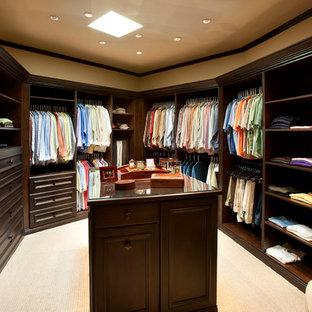 Foto de armario vestidor de hombre, tradicional, grande, con armarios con paneles con relieve, puertas de armario de madera en tonos medios y moqueta
