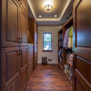 Foto de vestidor de hombre, mediterráneo, de tamaño medio, con armarios con paneles con relieve, puertas de armario de madera oscura, suelo marrón y suelo de madera oscura