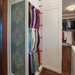 Idee per un grande spazio per vestirsi per donna mediterraneo con ante con bugna sagomata, ante bianche, pavimento in legno massello medio e pavimento marrone