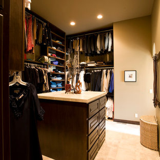 Inspiration for a large traditional gender neutral dressing room in Wichita with dark wood cabinets and travertine flooring.