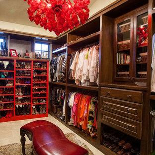 Large mediterranean gender neutral walk-in wardrobe in Austin with raised-panel cabinets, dark wood cabinets and travertine flooring.