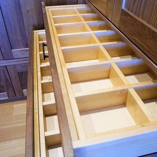 Modelo de armario vestidor unisex, rural, grande, con armarios estilo shaker, puertas de armario de madera oscura, suelo de madera clara y suelo beige