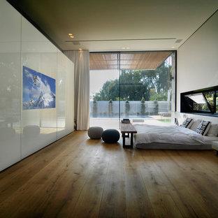 Idées déco pour un grand dressing room contemporain neutre avec un placard à porte vitrée, des portes de placard blanches et un sol en bois brun.