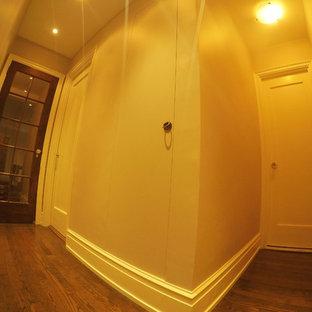 Ejemplo de armario unisex, moderno, de tamaño medio, con armarios con paneles empotrados, puertas de armario beige y suelo de madera clara