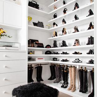 Esempio di una cabina armadio per donna contemporanea con ante lisce, ante bianche, parquet chiaro e pavimento beige