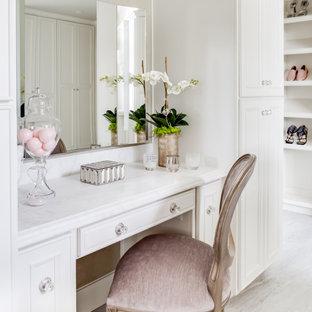 Idee per una grande cabina armadio per donna classica con ante con riquadro incassato, ante bianche, pavimento in marmo, pavimento bianco e travi a vista