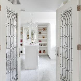 Cette photo montre un grand dressing chic pour une femme avec un placard avec porte à panneau encastré, des portes de placard blanches, un sol en marbre, un sol blanc et un plafond en poutres apparentes.