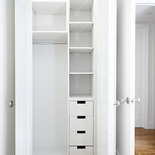 ニューヨークの小さい男女兼用コンテンポラリースタイルのおしゃれな壁面クローゼット (フラットパネル扉のキャビネット、白いキャビネット、淡色無垢フローリング) の写真